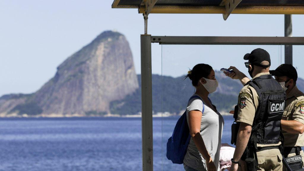 Los agentes verifican la temperatura de una mujer que usa una mascarilla después de bajarse de un autobús público, con la montaña Pan de Azúcar en el fondo, en la ciudad de Niteroi, durante su primer día de confinamiento, mientras continúa la propagación del Covid-19, cerca de Río de Janeiro, Brasil, el 11 de mayo de 2020.