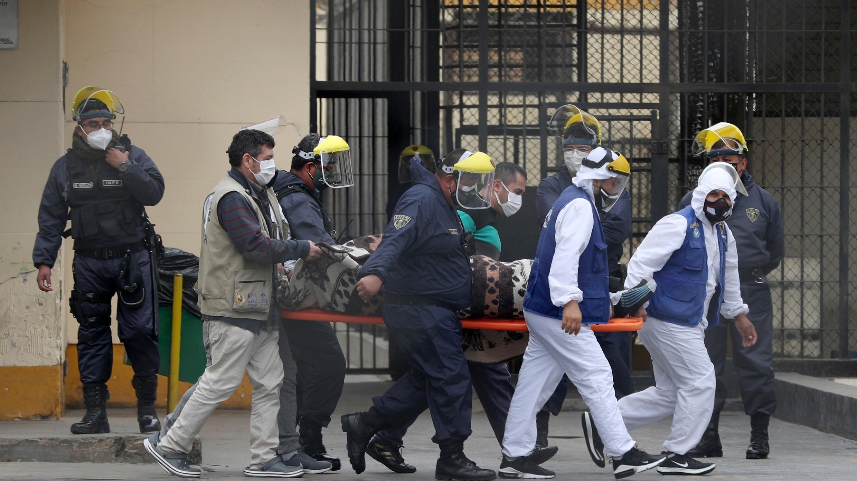 Reclusos vestidos con trajes protectores blancos y agentes de seguridad transportan a un reo a una clínica en la prisión de Lurigancho en las afueras de Lima, Perú, el miércoles 19 de agosto de 2020.