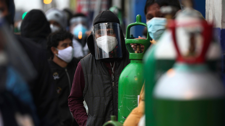 La gente espera en línea con sus cilindros de oxígeno vacíos para recargar en una tienda en el barrio San Juan de Lima, Perú, el lunes 3 de agosto de 2020.