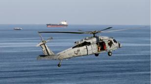 Imagen de archivo. Un helicóptero de la marina estadounidense vuela cerca a un petrolero que navega a través del estrecho de Hormuz, el 21 de diciembre de 2018.