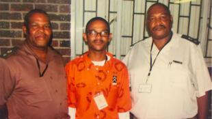 Welcome Witbooi, entouré de deux gardiens, pendant son incarcération à la prison de Drakenstein, en Afrique du Sud.