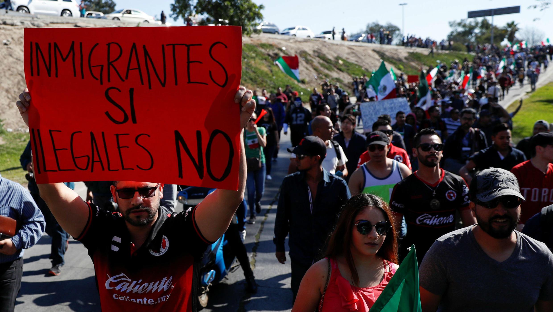 """Un manifestante que sostiene un cartel que dice """"Inmigrantes sí, ilegales no"""" asiste a una protesta contra los migrantes que forman parte de una caravana que viaja a Estados Unidos, en Tijuana, México, el 18 de noviembre de 2018."""