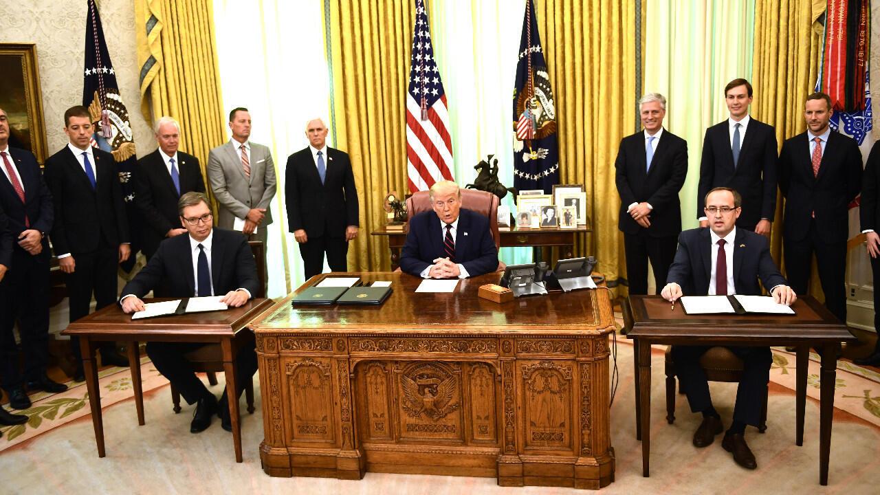 """الرئيس الصربي ألكسندر فوتشيتش ورئيس الوزراء الكوسوفي عبد الله هوتي في البيت الأبيض، في 4 سبتمبر/أيلول 2020، حيث وقعا  اتفاقا حول """"التطبيع الاقتصادي""""."""