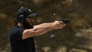 "Rabbi Raziel Cohen, aka ""Tactical Rabbi,"" shoots a Glock 9 mm pistol during a demonstration at the Angeles Shooting Ranges in Pacoima, California on May 20, 2019"