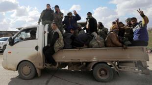 Miembros de las Fuerzas Democráticas Sirias hacen gestos desde un camión en la ciudad de Al Baguz, donde están llevando a cabo un ataque contra el grupo Estado Islámico, el 17 de febrero de 2019.