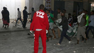 صوماليون يحملون مصابا أمام فندق مكة المكرمة في العاصمة الصومالية 01 مارس/آذار 2019