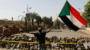 أحد المتظاهرين السودانيين يلوح بعلم بلاده بأحد الحواجز أمام قيادة الجيش