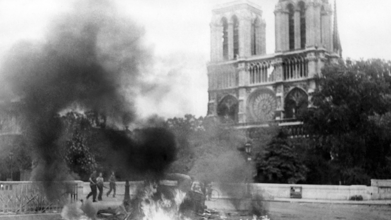 """Una foto tomada entre el 22 y el 24 de agosto de 1944 en París durante la Segunda Guerra Mundial muestra un vehículo en llamas cerca del Pont Saint-Michel y la catedral Notre-Dame parte de la """"Batalla de París"""" que se opone a la FFI (Fuerzas francesas del Interior)"""