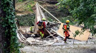 Des secouristes passent devant une tente détruite par les intempéries qui ont touché Saint-Julien-de-Peyrolas et la région, le 9 août 2018.