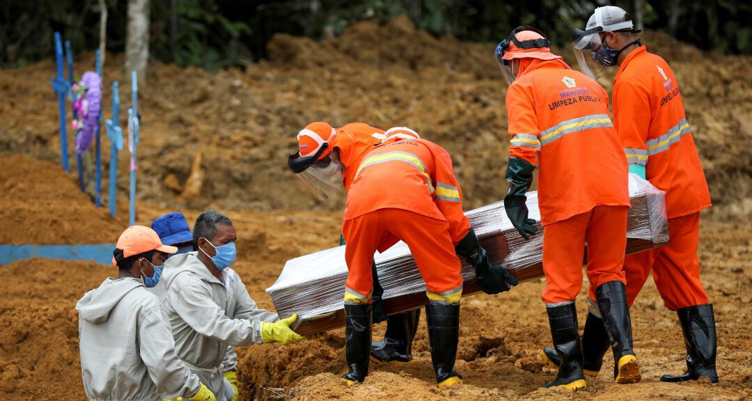 Trabajadores de una cementerio hacen un entierro masivo de personas fallecidas por coronavirus. Manaus, Brasil, el 13 de mayo de 2020.