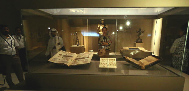 Des exemplaires du Coran, retrouvés dans la capitale syrienne Damas et datant du XIIIe siècle. A l'arrière-plan, une statue du Christ montrant ses blessures (Autriche, vers 1515) et une statuette malienne (1228-1295).