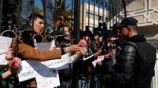 أحد الطلاب يقدم زهرة لقوات الأمن خلال مظاهرة ضد العهدة الخامسة لبوتفليقة - 3 مارس/ آذار 2019