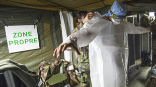 Une militaire aide un collègue à enfiler une blouse de protection sans la contaminer, le 24 mars 2020 à l'hôpital de campagne destiné à accueillir les malades du Covid-19, à Mulhouse
