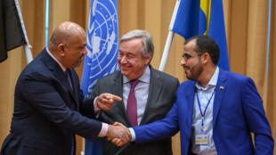 Le ministre des Affaires étrangères yéménite, Khaled al-Yamani (à gauche), et le négociateur pour les rebelles, Mohammed Abdelsalam (à droite), se serrent la main devant Antonio Guterres (ONU), le 13 décembre 2018.