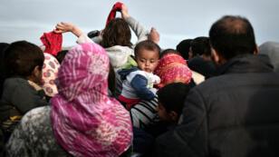 Des migrants essayent de récupérer des vêtements près de la frontière gréco-macédonienne, le 6 mars 2016.