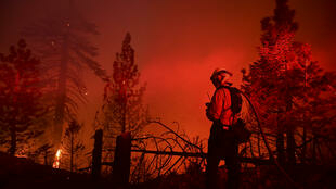 A firefighter watches as the Bobcat Fire burns near Cedar Springs in the Angeles National Forest on September 21, 2020, in Los Angeles, California.
