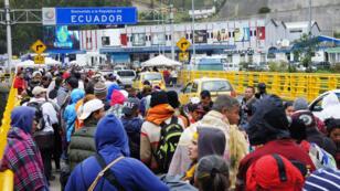 Migrantes venezolanos esperan en la frontera con Colombia, en el paso de Rumichaca (Ecuador), el 22 de agosto de 2019, antes de que entre en vigor la exigencia de visas para las personas de esa nacionalidad, el 26 de agosto de 2019.