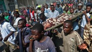Des manifestants transportent un cadavre à Goma, samedi