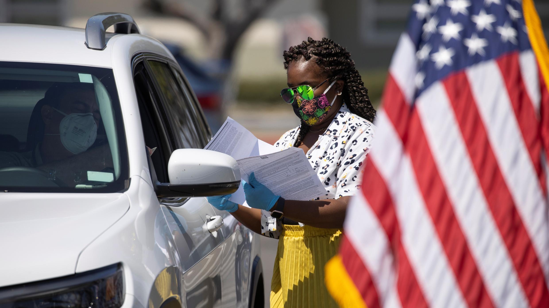Un oficial de inmigración de EE. UU. Ayuda a organizar los vehículos que llegan durante la juramentación de ciudadanos estadounidenses recién naturalizados en Santa Ana, California, EE. UU., 29 de julio de 2020.