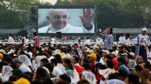 Cientos de asistentes escuchan la misa campal que ofreció el papa Francisco en el estadio de fútbol Kyaikkasan, en Rangún (Myanmar).