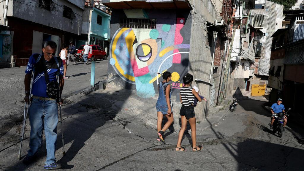 La gente camina y pasa un mural pintado por Fabian Solymar en el barrio pobre de Petare, en Caracas, Venezuela, el 7 de agosto de 2019.