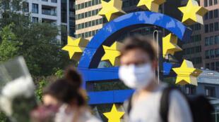 Dos personas con mascarilla frente al símbolo del euro en Fráncfort, Alemania, el 24 de abril de 2020