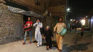 المسحراتي سيد مزاحم يقرع على طبلته لإيقاظ الصائمين في أحد أحياء بغداد في السابع من أيار/مايو 2020