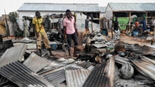 عناصر من قوات الدفاع الذاتي يتفقدون الأضرار الناجمة عن اعتداء انتحاري في مايدوغوري في 8 حزيران/يونيو.