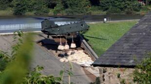 طائرة هليكوبتر من طراز شينوك تسقط الأكياس الرملية فوق المنطقة المنهارة في جسر وايلي، بريطانيا في 2 أغسطس/آب 2019.