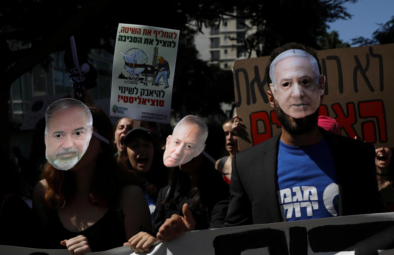 Manifestantes usan máscaras del primer ministro Benjamin Netanyahu, Benny Gantz y Avigdor Liberman, mientras participan en una protesta contra el cambio climático durante un evento en Tel Aviv, Israel.