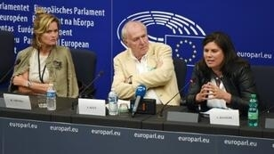 النائبتان الأوروبيتان هيلغا تروبيل (يسار) وفيرجيني روزيير (يمين) والصحافي في وكالة فرانس برس سامي كيتز (وسط) في مؤتمر صحافي في البرلمان الأوروبي في بروكسل في 11 أيلول/سبتمبر 2018