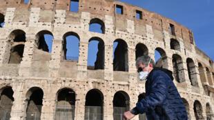 En pleine épidémie du coronavirus, un homme portant un masque sanitaire passe devant le Colysée de Rome.