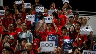 "Hong Kong fans hold up signs that read ""Boo"" in 2015 during China's national anthem before a qualifying match for the 2018 World Cup at Mong Kok stadium in Hong Kong"