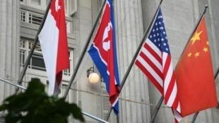 Las banderas de Singapur, Corea del Norte, EE. UU. y China en la fachada del Hotel Fullerton, lugar de la cumbre Trump-Kim.