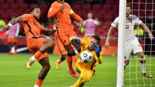 El portero de Polonia Bartlomiej Dragowski (D) evita la caída de su arco ante la arremetida del delantero holandés Memphis Depay (I), en partido de la Liga de Naciones jugado el 4 de septiembre de 2020 en Ámsterdam