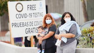 Deux femmes et un enfant attendent pour un test au Covid-19 à l'Université Charles Drew, le 22 juillet 2020, à Los Angeles.