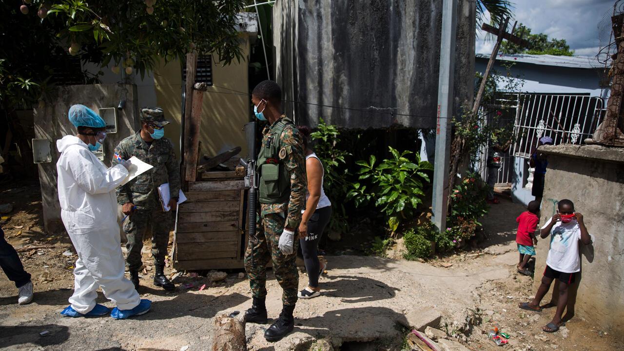 Un soldado hace guardia al personal del Servicio Nacional de Salud que realiza pruebas en la población para detectar casos de Covid-19 en San Cristóbal, uno de los lugares más afectados en República Dominicana durante la pandemia de coronavirus, el 13 de junio de 2020.