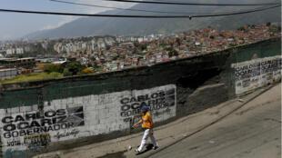 Un habitante pasa caminando frente a una pintada de campaña del candidato opositor a la gobernación de Miranda, Carlos Ocariz, de cara a las elecciones regionales, el 13 de octubre de 2017.