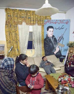 """Légende : """"Le martyr Kayed Abu Mustafa dans le salon familial. On y lit 'La panthère de Kata'ib Chuhada' al-Aqsa' ('Mikere, des Brigades des martyrs d'al-Aqsa'). Dans la pièce se trouve la mère de Mikere, son petit neveu et ses deux enfants."""""""