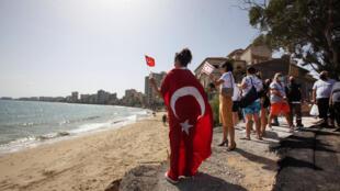 """امرأة تلوح بعلم تركي وعلم """"جمهورية شمال قبرص التركية"""" لدى دخولها مع عدد من الاشخاص إلى ساحل فاروشا، في المنطقة المسيجة بفماغوستا في الشطر الذي تحتله تركيا من قبرص، في 8 تشرين الأول/أكتوبر"""