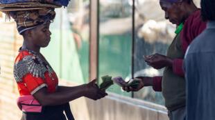 Unos vendedores intercambian dinero en un mercado de Bulawayo, en Zimbabue, el 31 de marzo de 2020