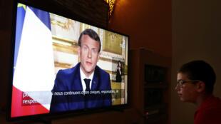 Un joven mira por televisión el discurso del presidente francés Emmanuel Macron en Montpellier, Francia, el 13 de abril de 2020.