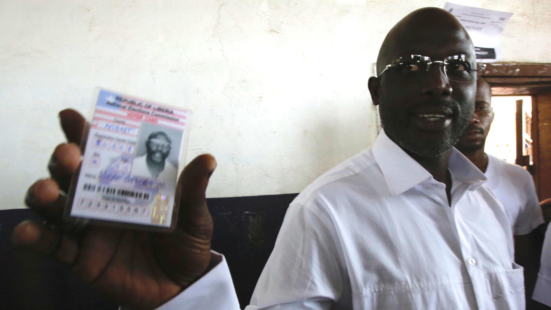 George Weah, exjugador de fútbol y candidato presidencial del Congreso para el Cambio Democrático (CDC), muestra su tarjeta de votante en una mesa de votación en Monrovia, Liberia. 10 de octubre de 2017