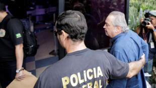 El exministro de Agricultura de Brasil, Wagner Rossi, es escoltado por un oficial al llegar a la sede de la policía federal en Sao Paulo, Brasil, el 29 de marzo de 2018.