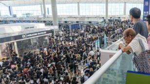 Les manifestants prodémocratie bloquent l'accès aux zones d'embarquement de l'aéroport international de Hong Kong, le 13août2019.