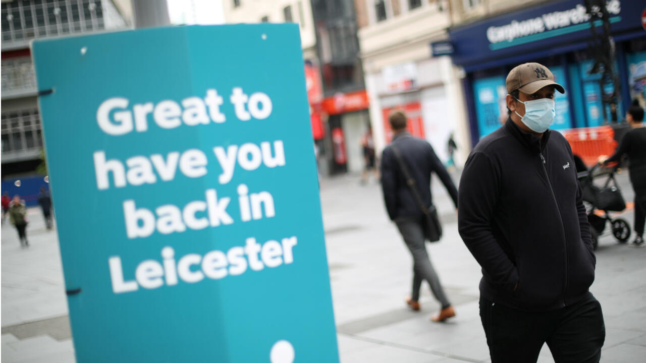 A man wearing a protective mask walks past a sign, amid the coronavirus disease (COVID-19) outbreak, in Leicester, UK, on June 29, 2020.