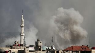 Una foto tomada el 20 de febrero de 2018 muestra columnas de humo que se elevan después de un ataque aéreo reportado por las fueras progubernamentales sirias en la ciudad de Hamouria, controlada por los rebeldes, en la sitiada región de Guta Oriental, en las afueras de la capital, Damasco.
