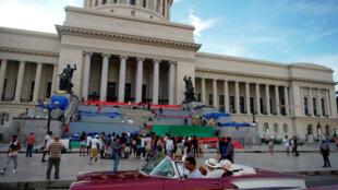 Los turistas en un automóvil antiguo pasan por el Capitolio en La Habana, Cuba, el 9 de noviembre de 2019.