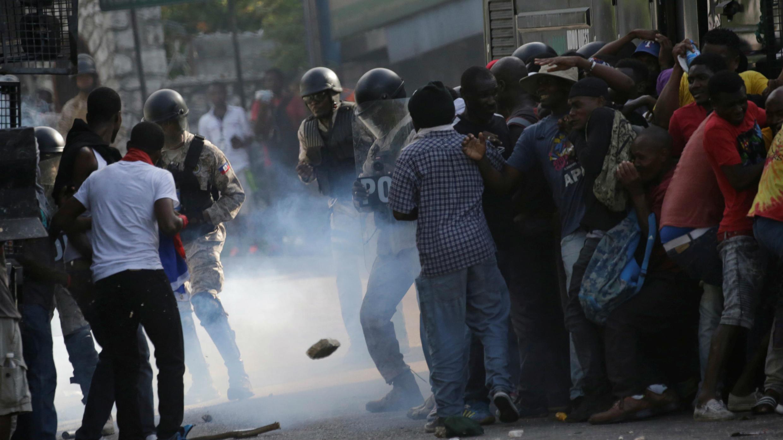 Manifestantes se esconden detrás de un camión antidisturbios, durante enfrentamientos en una manifestación para exigir la renuncia del presidente Jovenel Moïse, en las calles de Puerto Príncipe, Haití, 11 de octubre de 2019.
