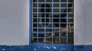 A prisoner looks out from behind a grate in his cell at Haiti's national penitentiary in Port-au-Prince in August 2019
